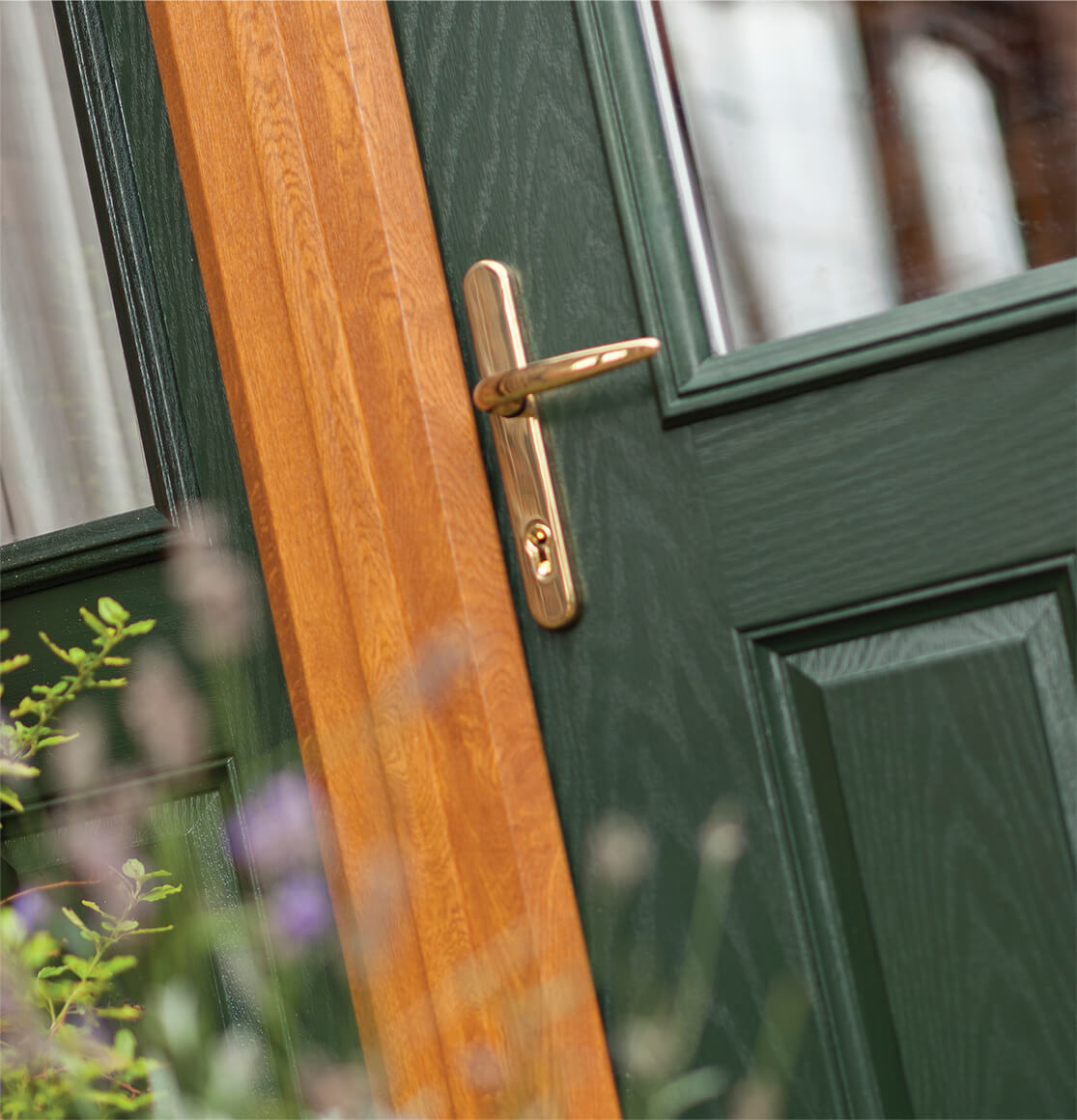 green composite door with frame and gold effect handle